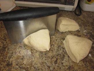 Dividing the dense dough into equal portions.
